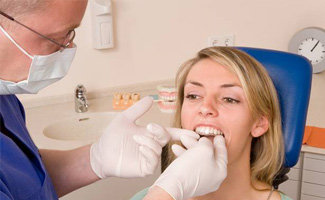 Dentist placing woman's Invisalign tray