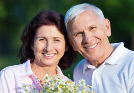 Smiling older man and woman outdoors holding flowers