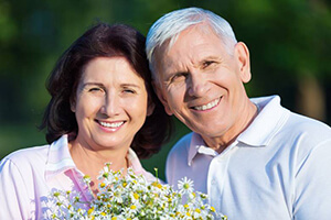 Smiling man and woman outdoors holding flowers