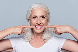 Senior woman pointing to flawless smile